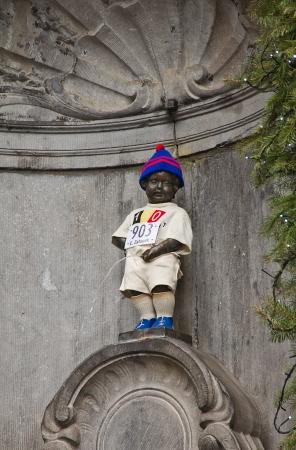 belgie: Famous statue Manneken Pis (circa 1619) dressed in sport uniform (in honor of Emil Zatopek, Czech long-distance runner). Brussels, Belgium