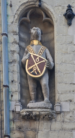 belgie: Figure of bear holding the coat of arms (emblem of jousting association %uFFFDDe Witte Beer%uFFFD). Facade of Poortersloge (Burghers%uFFFD Lodge) building (circa XV c.). Historic center of Bruges , West Flanders, Belgium Editorial