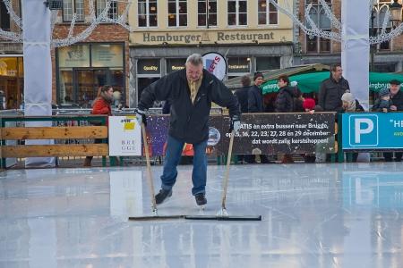 belgie: Manual cleaning of skating-rink. Grote Markt square, Bruges, West Flanders, Belgium