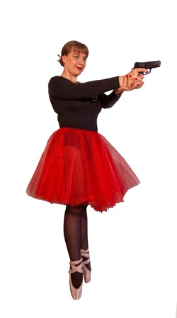 Young attractive woman in black-red ballerina dress holds black gun by two hands on isolated background Stock Photo