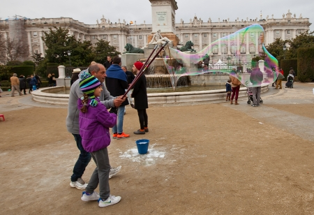 deftness: Street animator demonstrating to happy girl magic of huge soap bubbles during New Year celebrations  Oriente square, Madrid, Spain