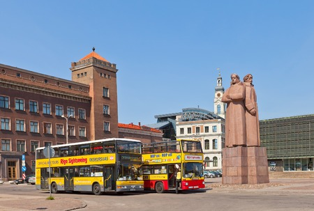 storied: Riga, Latvia - May 25, 2014  Two yellow double-decker city sightseeing buses waiting for tourists on the Latvian Riflemen square in Riga, Latvia Editorial