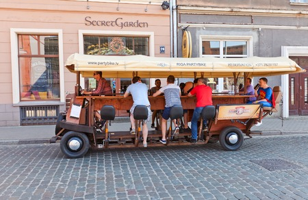 Riga, Latvia - May 25, 2014  Partybus Beer Bike with bar attendants on the street of Riga, Latvia  It is a pedal powered bar on the wheels  As the bar attendants pedal the barman is steering