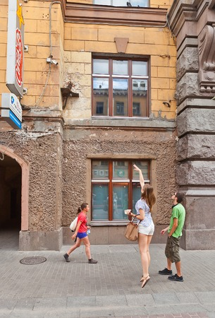 malaya: Russia, Saint Petersburg - July 14, 2014  Young woman tries to throw coin to small platform with statue of cat Elisey  According to popular belief success throw will bring a lot of luck  Malaya Sadovaya street, Saint Petersburg, Russia