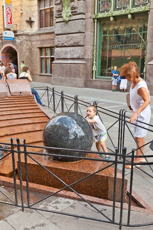 malaya: Russia, Saint Petersburg - July 14, 2014  Kid rolls big granite sphere of fountain on Malaya Sadovaya street in Saint Petersburg  According to popular belief it will bring a lot of luck