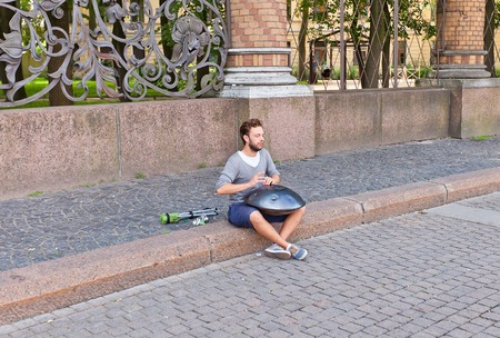 representations: Russia, Saint Petersburg - July 12, 2014  Street musician playing idiophone musical instrument named Hang in Saint Petersburg, Russia Editorial