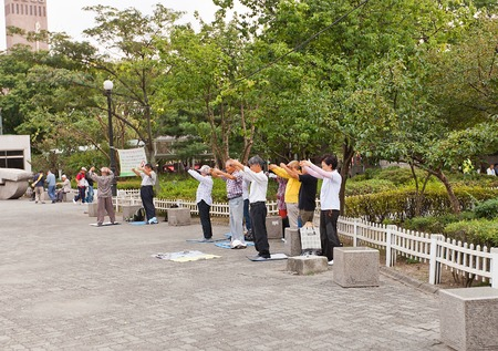 koreans: SEOUL, SOUTH KOREA - SEPTEMBER 27, 2014: Senior Koreans make exercises of traditional Korean gymnastics Dankhak on the street of Seoul, Korea Editorial