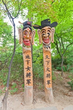 worshipped: SEOUL, SOUTH KOREA - SEPTEMBER 28, 2014: Jangseung totem poles in Namsangol Hanok Village museum of Seoul, Korea. Jangseung frighten away demons and worshipped as village tutelary deities Editorial