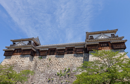besiege: MATSUYAMA, JAPAN - MAY 21, 2015: North and South Corner Turrets connected by hallway Jikken-Rouka in Iyo Matsuyama castle, Shikoku Island, Japan. Erected in 1603, reconstructed in 1968. National Historic Site