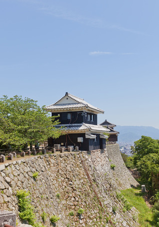 besiege: MATSUYAMA, JAPAN - MAY 21, 2015: Bagu (Horse Gear) Turret (erected in 1603, reconstructed in 1958) of Iyo Matsuyama castle, Shikoku Island, Japan. National Historic Site