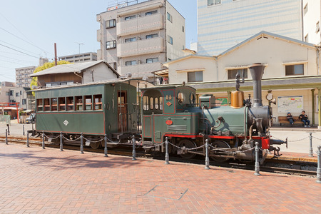 MATSUYAMA, JAPAN - MAY 21, 2015: Botchan train near Dogo Onsen station in Matsuyama, Japan. Botchan Ressha is a diesel-powered replica of a German small-gauge steam locomotive installed in 1888 新聞圖片