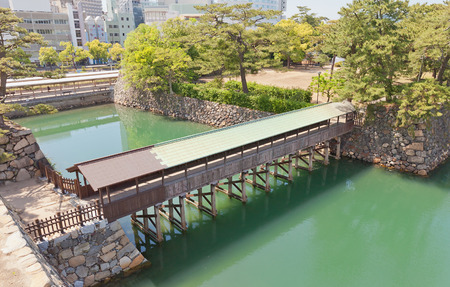 besiege: TAKAMATSU, JAPAN - MAY 22, 2015: Saya-bashi bridge of Takamatsu castle, Shikoku Island, Japan. Constructed in 1640, reconstructed in 2011 Editorial