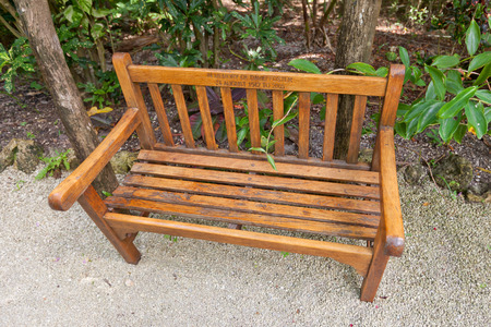 overseas: GRAND CAYMAN - JUNE 28, 2015: Commemorative bench in Queen Elizabeth II Botanic Park of Grand Cayman, Cayman Islands (British Overseas Territory). Made in memory of David Foster (1942-2005), founder of Foster Food Fair company Editorial