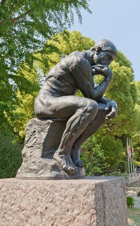 pensador: TOKIO, JAPÓN - 26 de mayo 2015: copia ampliada de la escultura Pensador (1880) por Auguste Rodin cerca de Museo Nacional de Arte Occidental en el parque Ueno de Tokio, Japón
