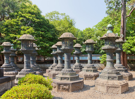 lords: TOKYO, JAPAN - MAY 26, 2015: Bronze lanterns (toro) in Ueno Toshogu Shinto Shrine in Tokyo, Japan. About 50 lanterns were donated by daimyo (feudal lords) during the Edo period