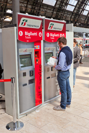MILAN, ITALY - APRIL 11, 2015: Man buying a ticket via self-service ticket machine in central railway station of Milan, Italy