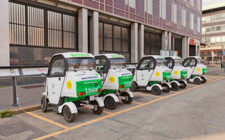 twoseater: MILAN, ITALY - APRIL 11, 2015: Charging of small two-seater electric automobiles in Milan, Italy Editorial