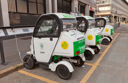 twoseater: MILAN, ITALY - APRIL 11, 2015: Three small two-seater electric automobiles charging on the street of Milan, Italy