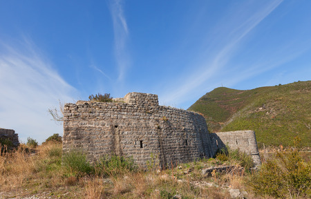 hardly: BUDVA, MONTENEGRO - FEBRUARY 02, 2016: Ruins of Mogren Fort on Mogren Cape near Budva town, Montenegro. Erected in 1860 by Austro-Hungarians, hardly damaged in earthquake of 1979 Editorial