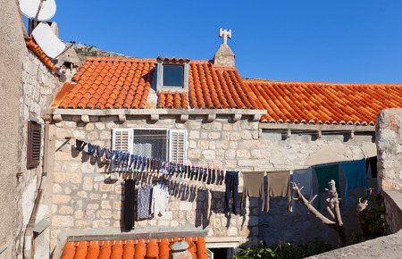 common people: DUBROVNIK, CROATIA - JANUARY 20, 2016: Laundry is drying on the facade of the house adjoined to city ramparts of Dubrovnik , Croatia. Medieval houses of Dubrovnik are still inhabited by common people