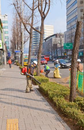 municipal editorial: SEOUL, SOUTH KOREA - MARCH 14, 2016: Municipal workers gather fallen leaves on the street of Seoul, Korea