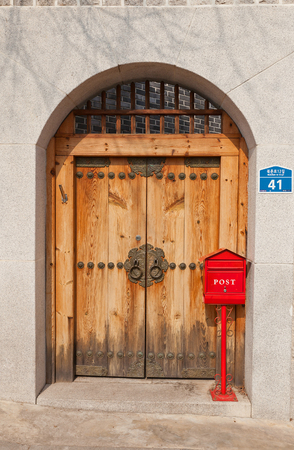 a traditional korean: SEOUL, SOUTH KOREA - MARCH 14, 2016: Retro style wooden door and red mail box in Folk Bukchon Hanok Village in Seoul, Korea. Hanok is a traditional Korean house