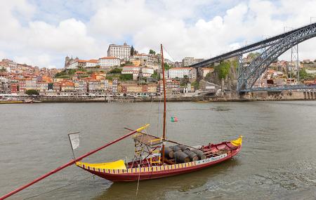 part of me: OPORTO, PORTUGAL - 25 de mayo, 2016: Barco tradicional Rabelo (portador de vino de Oporto) en el río Duero en Oporto, Portugal. Puente Dom Luis I y la parte histórica de la ciudad de Oporto en el fondo Editorial