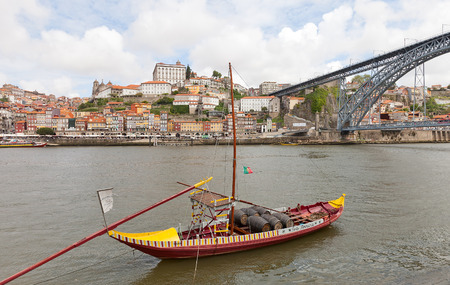 part of me: PORTO, PORTUGAL - MAY 25, 2016: Traditional Rabelo boat (port wine carrier) on Douro River in Porto, Portugal. Dom Luis I Bridge and historical part of Porto city at the background Editorial