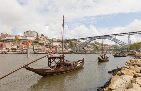 part of me: OPORTO, PORTUGAL - 25 de mayo, 2016: barcos tradicional Rabelo (transportadoras de vino de Oporto) en el río Duero en Oporto, Portugal. Puente Dom Luis I y la parte histórica de la ciudad de Oporto en el fondo Editorial