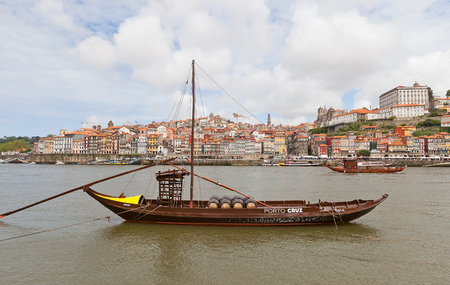 rabelo: PORTO, PORTUGAL - MAY 25, 2016: Traditional Rabelo boat (used for port wine transportation) at Douro River in Porto, Portugal. Historical part of Porto city at the background