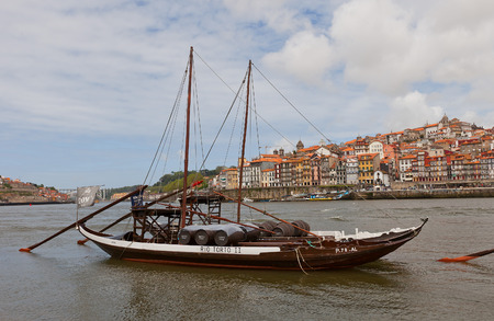 rabelo: PORTO, PORTUGAL - MAY 25, 2016: Traditional Rabelo boats (used for port wine transportation) on Douro River in Porto, Portugal. Historical part of Porto city at the background Editorial