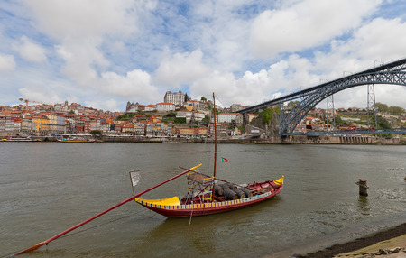 rabelo: PORTO, PORTUGAL - MAY 25, 2016: Traditional Rabelo boat (port wine carrier) on Douro River in Porto, Portugal. Dom Luis I Bridge and historical part of Porto city  at the background Editorial