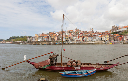 rabelo: PORTO, PORTUGAL - MAY 25, 2016: Traditional Rabelo boat (used for port wine transportation) on Douro River in Porto, Portugal. Historical part of Porto city at the background