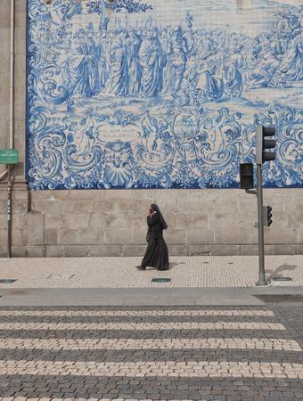 nun: PORTO, PORTUGAL - MAY 26, 2016: A nun walking by near Carmo Church in the historical center of Porto, Portugal