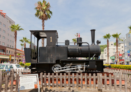 UWAJIMA, JAPAN - JULY 22, 2016: Steam locomotive Ke220 type on display outside Uwajima railway station, Shikoku Island, Japan. Made by Orenstein and Koppel OHG Company (Germany) Editorial