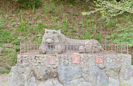 WAKAYAMA, JAPAN - JULY 23, 2016: Sculpture of a tiger (1959) at the entrance of Wakayama castle, Japan. Castle buildings resemble a tiger lying on Mount Torafusu side when seen from the ocean