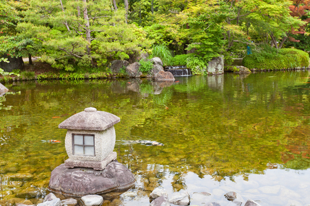 commemorate: HIMEJI, JAPAN - MAY 16, 2017: Traditional stone lantern (toro) on the pond of Kokoen Garden near Himeji castle, Japan. Garden was laid out in 1992 to commemorate 100 anniversary of Himeji city Editorial