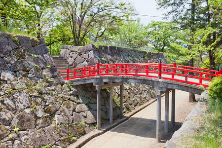 baileys: MARIOKA, JAPAN - MAY 22, 2017: Red bridge over the moat between main (honmaru) and second (ninomaru) baileys of former Marioka castle, Japan. Castle was constructed in 1633 and dismantled in 1874