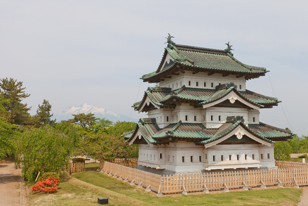 HIROSAKI, JAPAN - MAY 23, 2017: Main keep (donjon) of Hirosaki Castle with Mount Iwaki on the background. Was erected by Tsugaru Nobuhira in 1611, reconstructed in 1810, Important Cultural Property