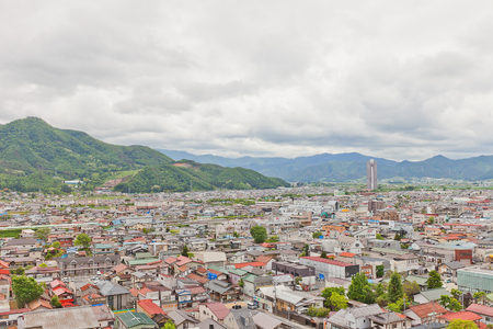 KAMINOYAMA, JAPAN - MAY 28, 2017: View of Sankichiyama Mount and Kaminoyama City from donjon of Kaminoyama Castle. Sky Tower 41 skyscraper is in the right corner