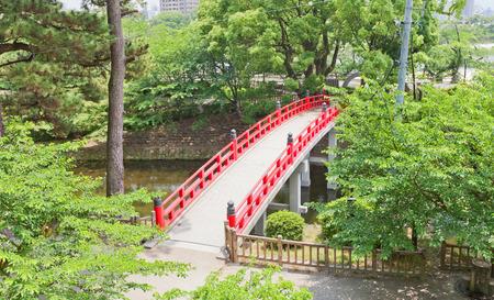 OKAZAKI, JAPAN - MAY 31, 2017: Red bridge over the moat of Okazaki Castle, Japan. Castle was founded in 1455 by Saigo Tsugiyori, shogun Tokugawa Ieyasu was born here in 1543