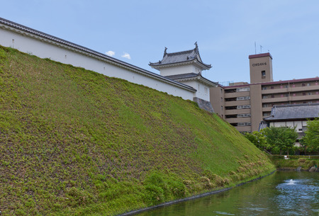 UTSUNOMIYA, JAPAN - JUNE 2, 2017: Reconstructed moat, earthen wall (dorui) and Fujimi Turret of Utsunomiya Castle, Japan. Castle was founded in 1062, destroyed in War of 1868 and reconstructed in 2007