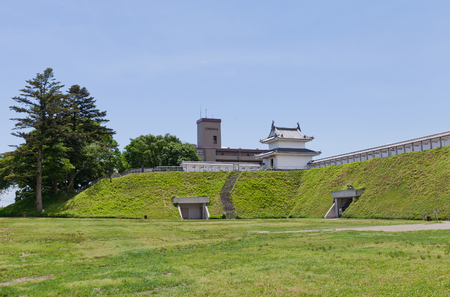 UTSUNOMIYA, JAPAN - JUNE 2, 2017: Reconstructed earthen wall and Fujimi Turret of Utsunomiya Castle, Japan. Castle was founded in 1062, destroyed in Boshin War of 1868 and reconstructed in 2007