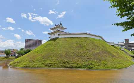 UTSUNOMIYA, JAPAN - JUNE 2, 2017: Reconstructed moat, earthen wall and Seimeidai Turret of Utsunomiya Castle, Japan. Castle was founded in 1062, destroyed in war of 1868 and reconstructed in 2007