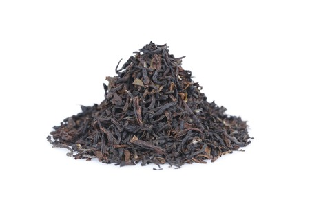 Het is Stapel van zwarte thee die op wit. Stockfoto