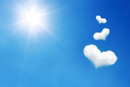 it is three heart shaped cloud on blue sky with sunshine. Stock Photo