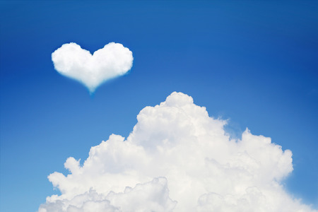 it is huge white cloud with heart shaped cloud. Stock Photo