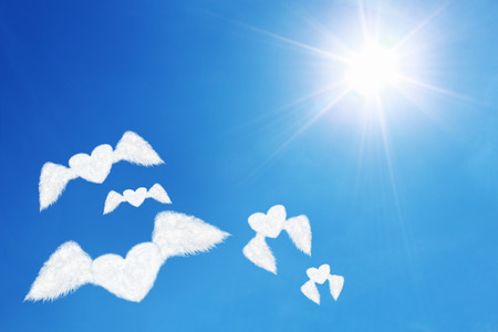 under heart: it is group of flying heart shaped clouds under sun shines.