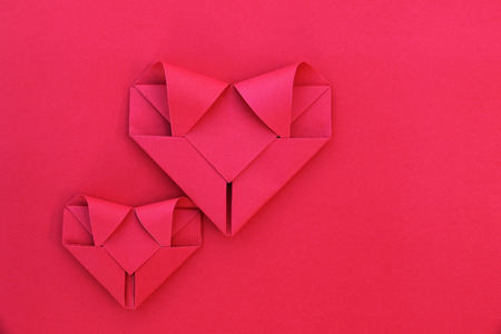 it is two folding red paper hearts on red for pattern and background.
