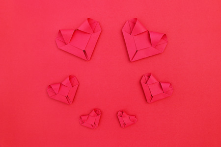 it is circle six folding red paper hearts on red for valentine pattern and background.